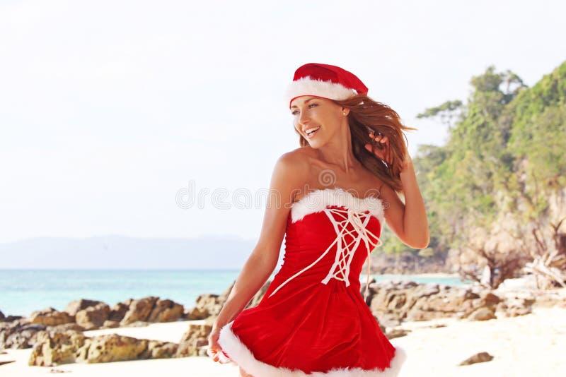 De vrouw van de Kerstman op strand stock afbeelding