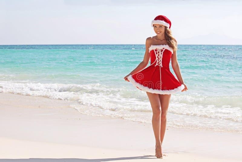 De vrouw van de Kerstman op strand stock foto's