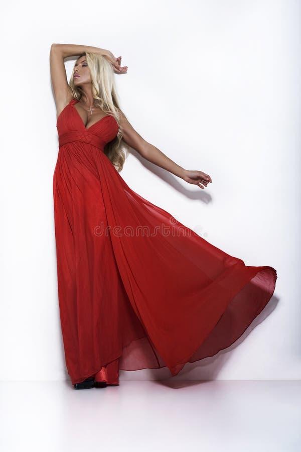 De vrouw van de luxe in rode kleding stock foto's