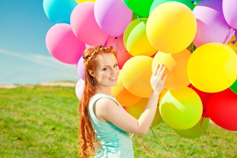 De vrouw van de luxemanier met ballons in hand op het gebied tegen royalty-vrije stock foto's
