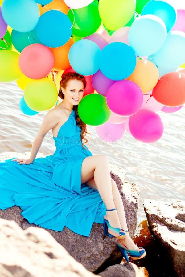De vrouw van de luxemanier met ballons in hand op het strand tegen stock foto's