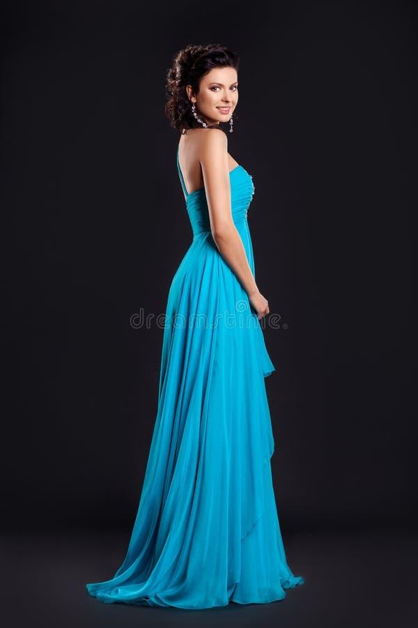 De vrouw van de manier in het funky blauwe lange kleding glimlachen stock foto's