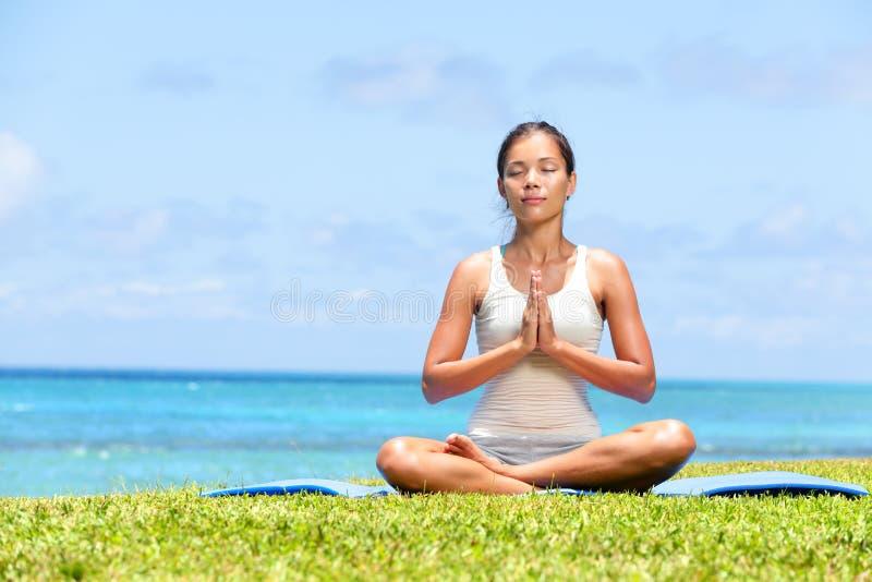 De vrouw van de meditatieyoga op strand die door oceaan mediteren stock afbeeldingen