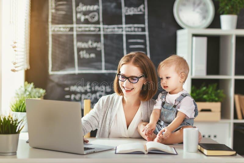 De vrouw van de onderneemstermoeder met peuter het werken bij computer royalty-vrije stock fotografie
