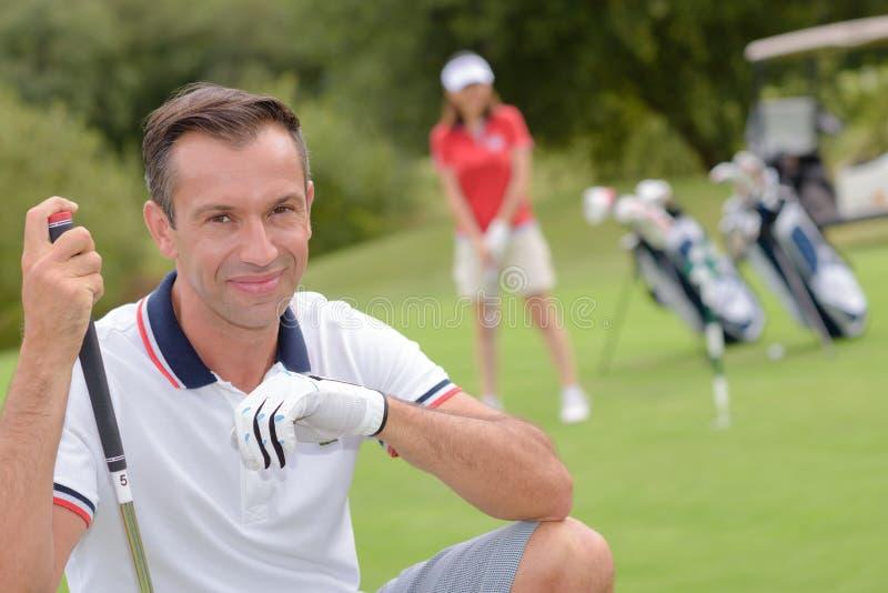 De vrouw van de portret het mannelijke golfspeler spelen op achtergrond stock foto's