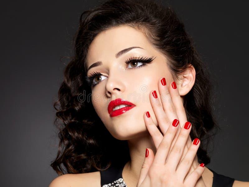 De vrouw van de schoonheidsmanier met rode spijkers en make-up stock foto