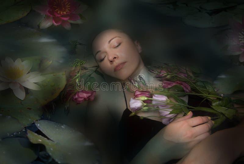 De vrouw van de slaap in een donker water van een rivier stock afbeelding