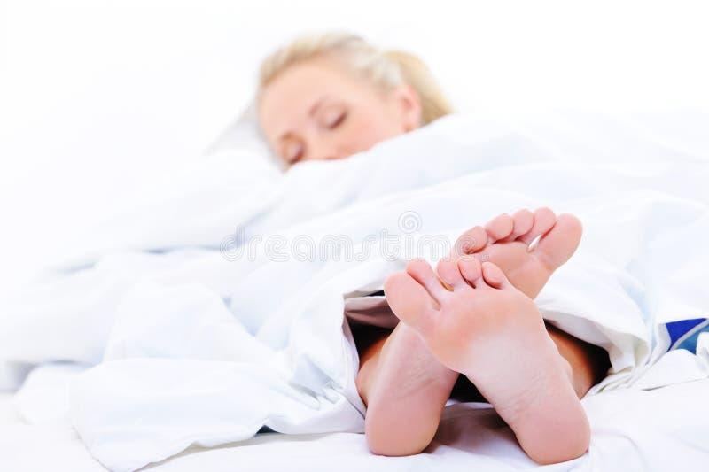 De vrouw van de slaap met voeten op voorgrond royalty-vrije stock fotografie