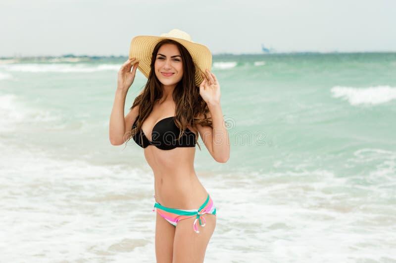 De vrouw van de strandvakantie in zon gelukkig glimlachen stock afbeeldingen