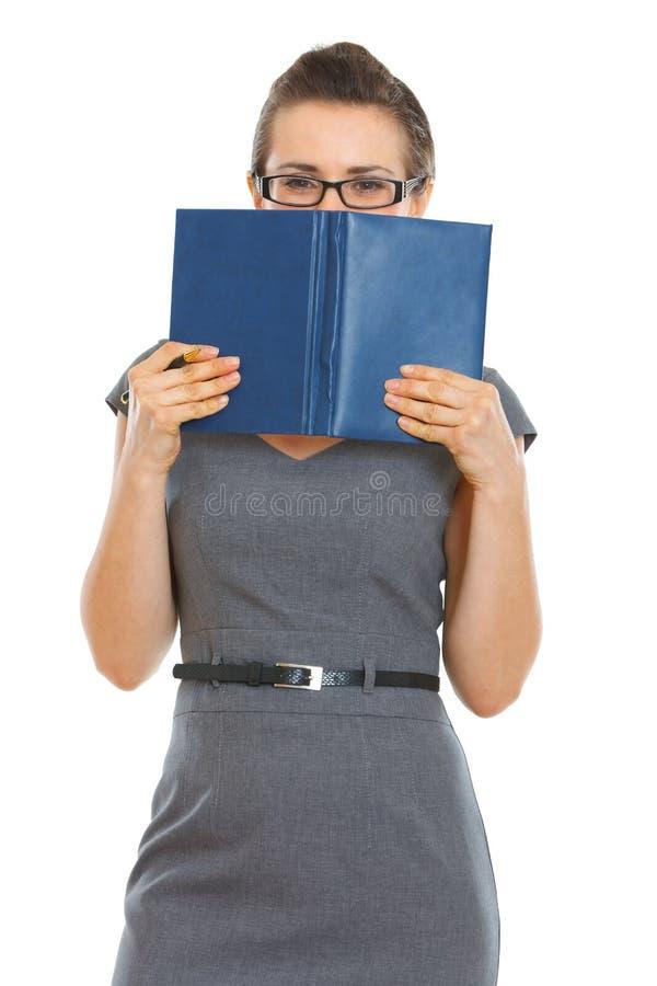 De vrouw van de student het verbergen achter notitieboekje