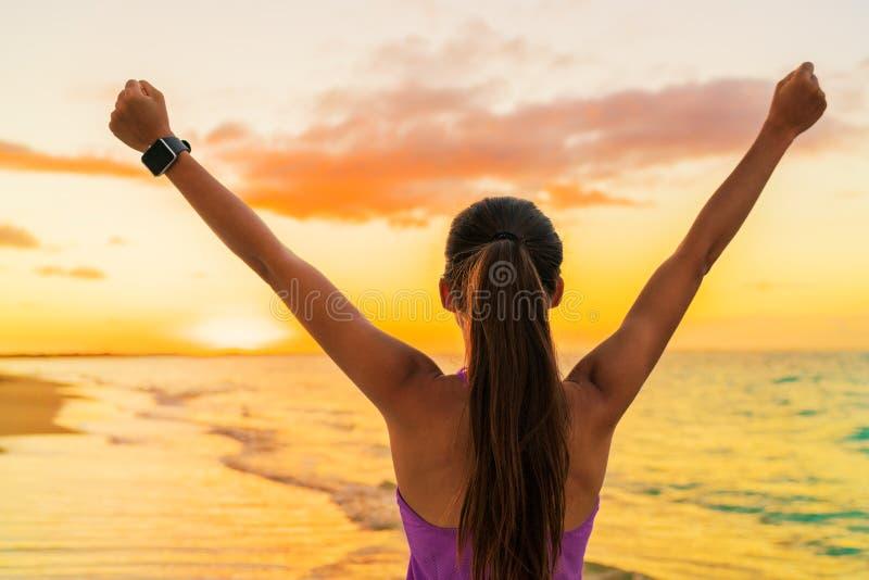 De vrouw van de succesvrijheid smartwatch bij strandzonsondergang stock foto's