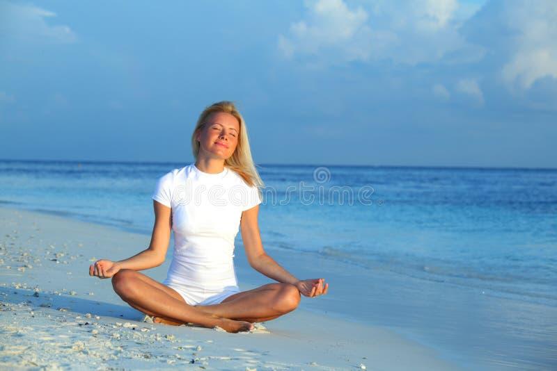 De vrouw van de yoga op overzeese kust royalty-vrije stock fotografie
