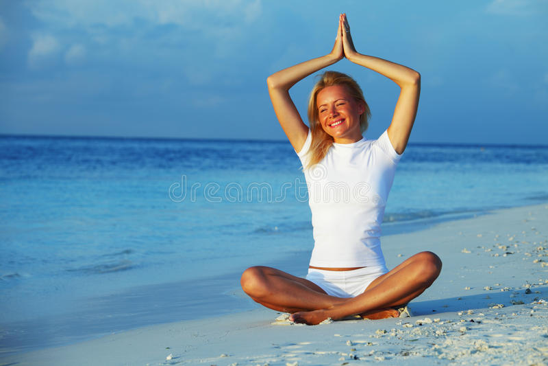 De vrouw van de yoga op overzeese kust stock afbeelding