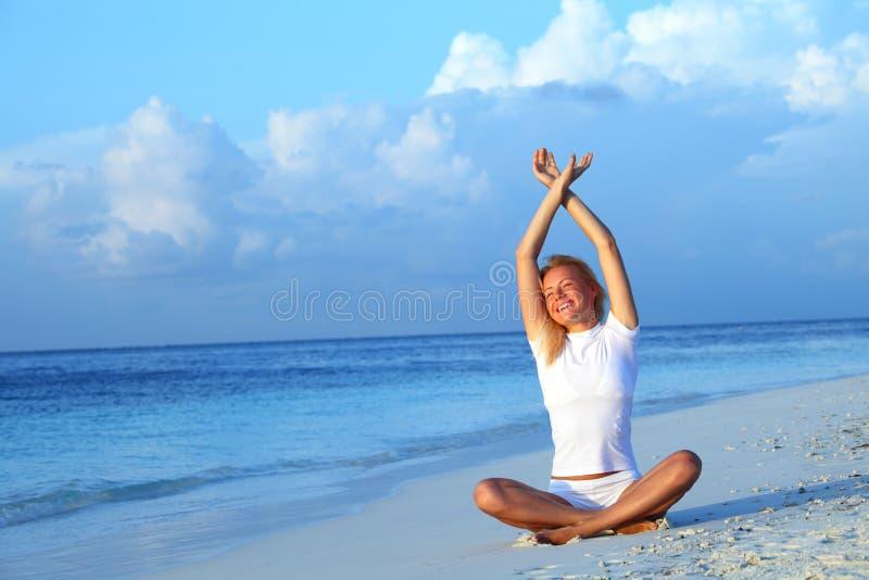 De vrouw van de yoga op overzeese kust royalty-vrije stock foto