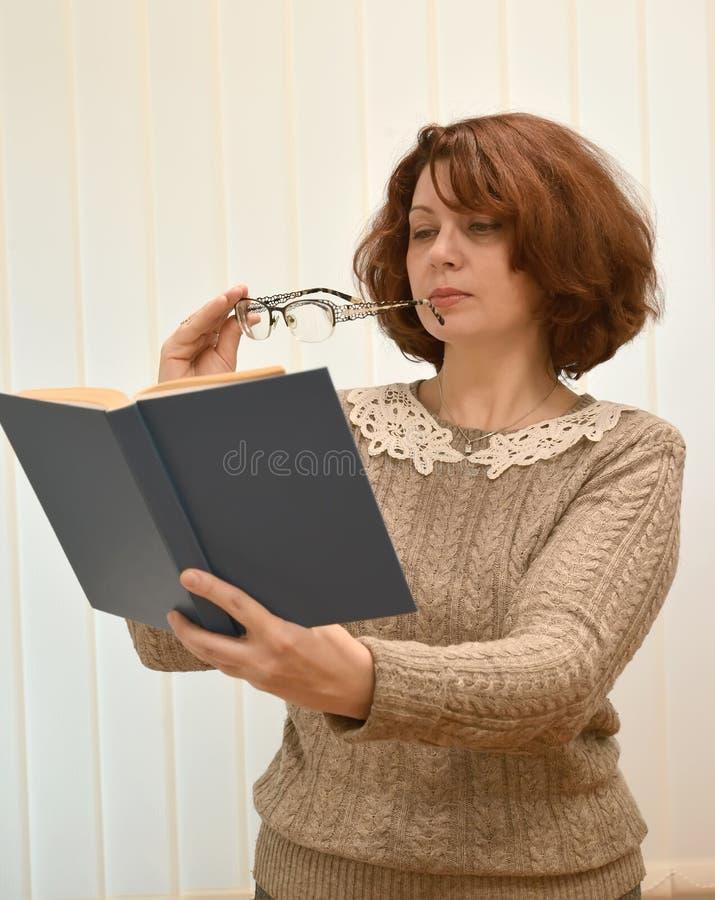 De vrouw van gemiddelde jaren leest het boek, houdend glazen in hand royalty-vrije stock afbeelding