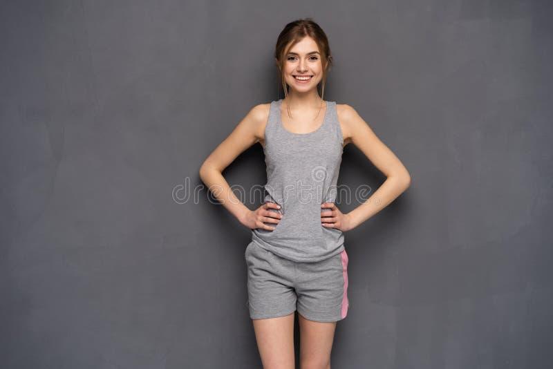 De vrouw van de geschiktheid Jong sportief Kaukasisch vrouwelijk die model op grijze achtergrond wordt geïsoleerd stock fotografie