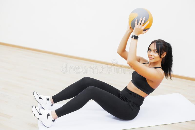 De vrouw van de geschiktheid Jonge aantrekkelijke vrouw die oefeningen doen die bal gebruiken stock afbeeldingen