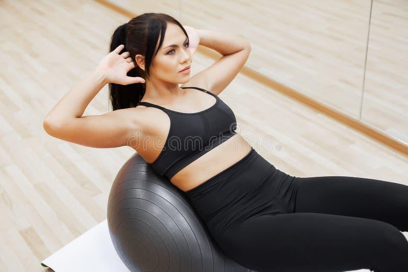 De vrouw van de geschiktheid Jonge aantrekkelijke vrouw die oefeningen doen die bal gebruiken royalty-vrije stock foto