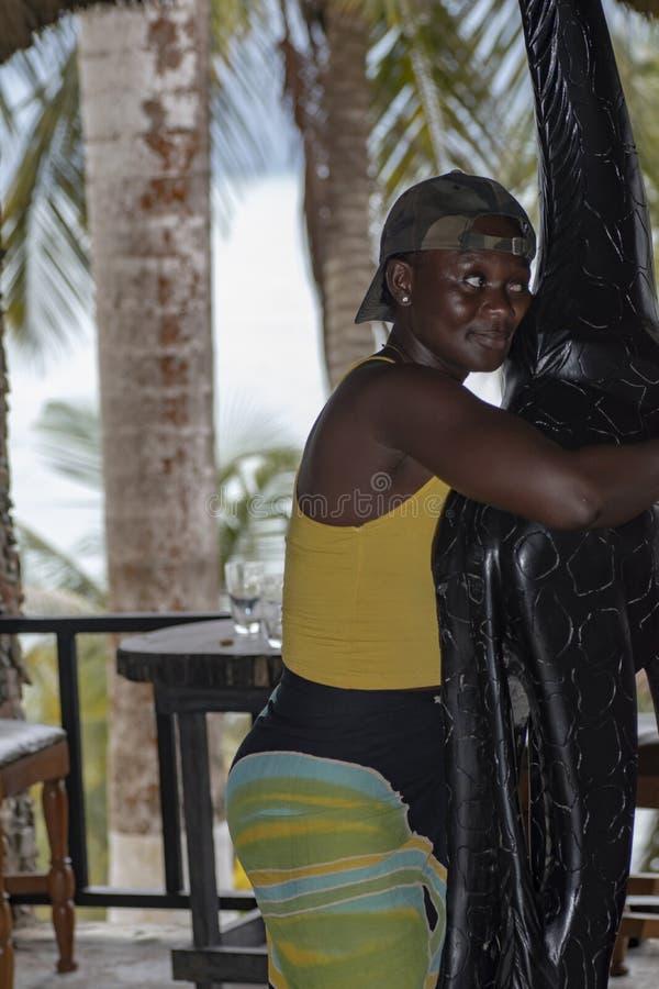 De vrouw van Ghana koestert een giraf in hout die zich binnen vraagt restaurant bevinden stock foto