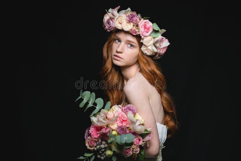 De vrouw van het Attrativeroodharige het stellen met bloemen royalty-vrije stock fotografie