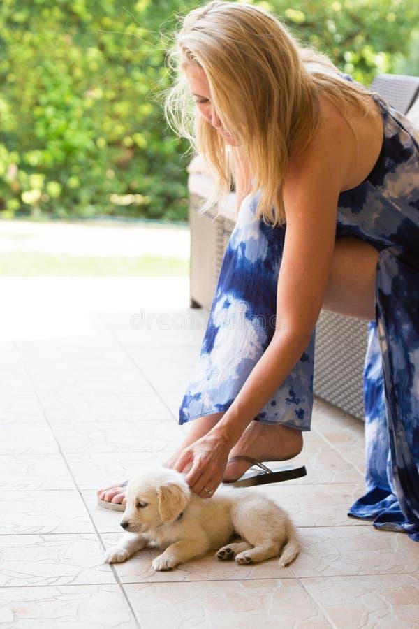 De vrouw van het Beuatifulblonde met de zeer jonge hond van het golden retrieverpuppy openlucht stock foto's