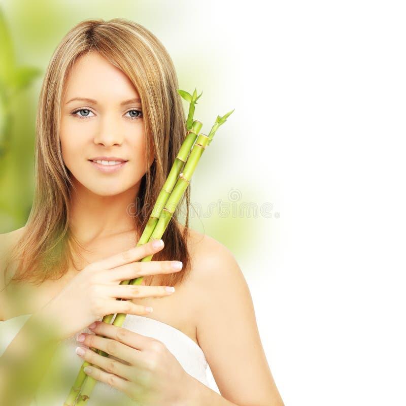 De vrouw van het kuuroord met bamboe stock afbeeldingen