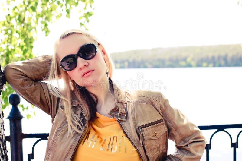 De vrouw van het manierblonde in lichtbruin leerjasje en zonnebril die voor het meer stellen stock foto