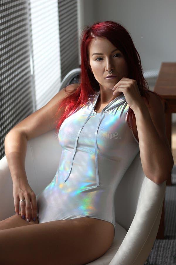 De vrouw van het youndroodharige in de holografische bovenkant met kap stock afbeeldingen