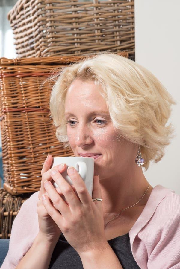 De Vrouw van het zittingsblonde glimlacht met Tevredenheid terwijl Hete Holding royalty-vrije stock afbeeldingen