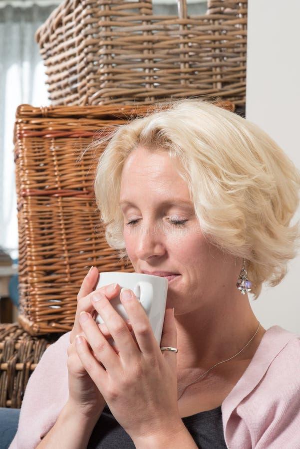 De Vrouw van het zittingsblonde sluit Ogen in Tevredenheid met Hete Drank stock foto's