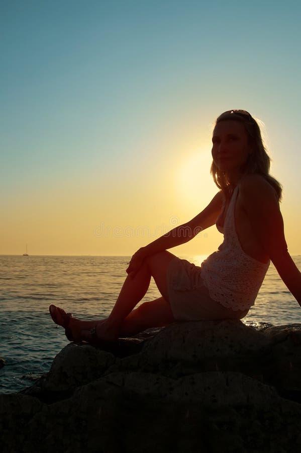 De vrouw van het zonsondergangsilhouet royalty-vrije stock afbeelding