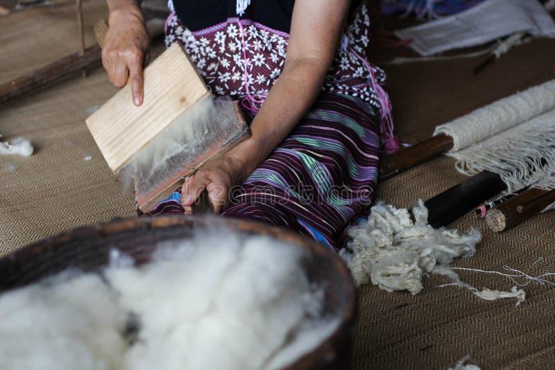 De vrouw van Karen het borstelen wolgaren met speciale borstel stock afbeelding