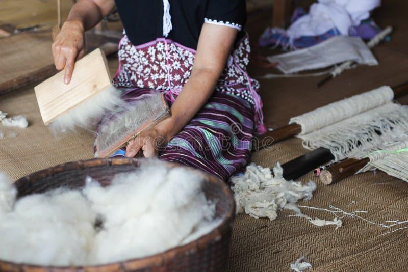 De vrouw van Karen het borstelen wolgaren met speciale borstel stock afbeeldingen