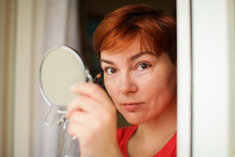 De vrouw van de make-upschoonheidsverzorging De volwassen vrouw onderzoekt spiegel en het zetten van de kleur van het oogpotlood  royalty-vrije stock afbeeldingen