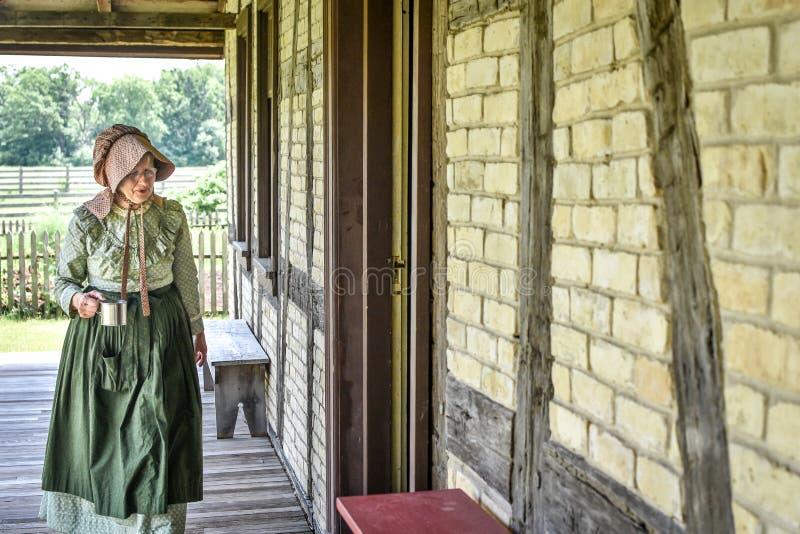 De Vrouw van de pioniersgezinshulp met Tin Coffee Mug stock afbeelding