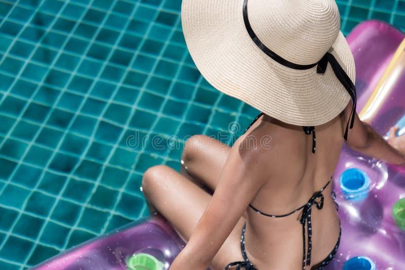 De vrouw van portretbeautifu het ontspannen in grote hoed en bikinizitting B stock afbeelding