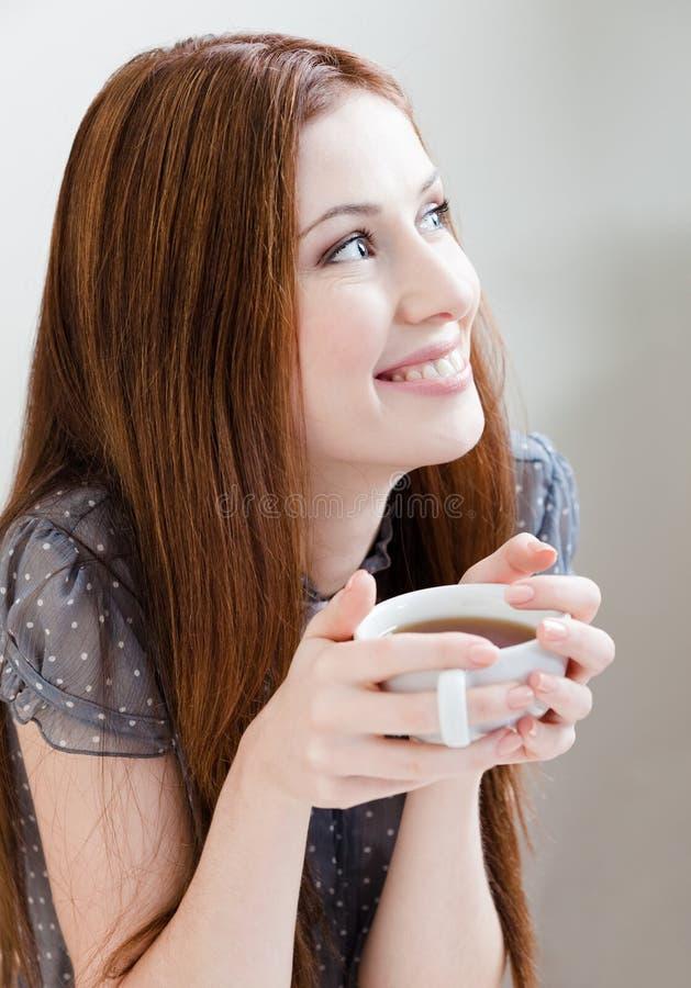 De vrouw van Smiley met kop thee stock foto's
