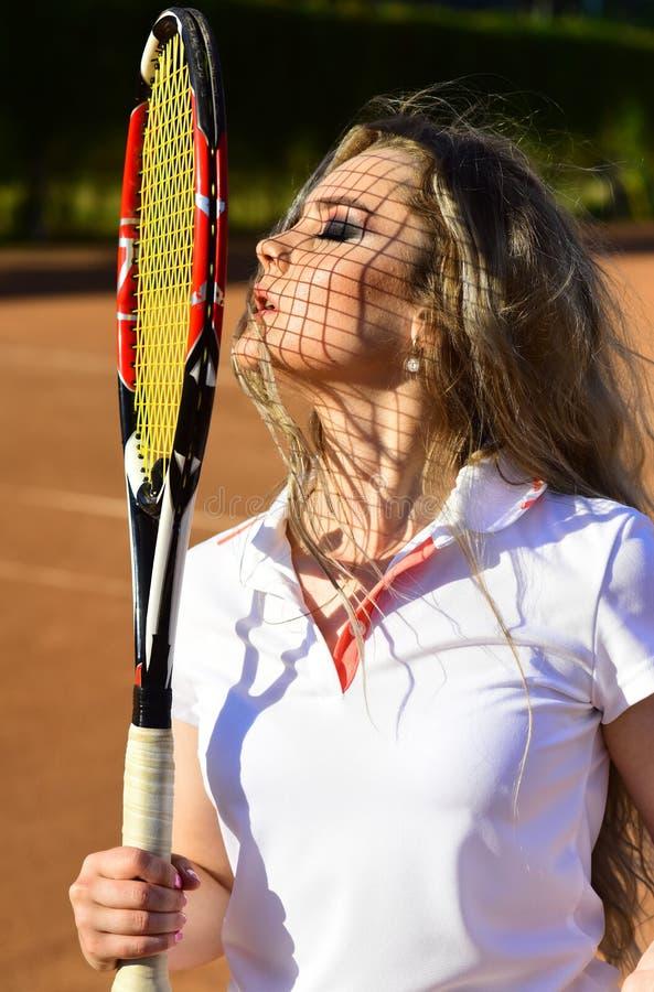 De vrouw van de tennisspeler sunbath met racket netto schaduw op gezicht royalty-vrije stock foto