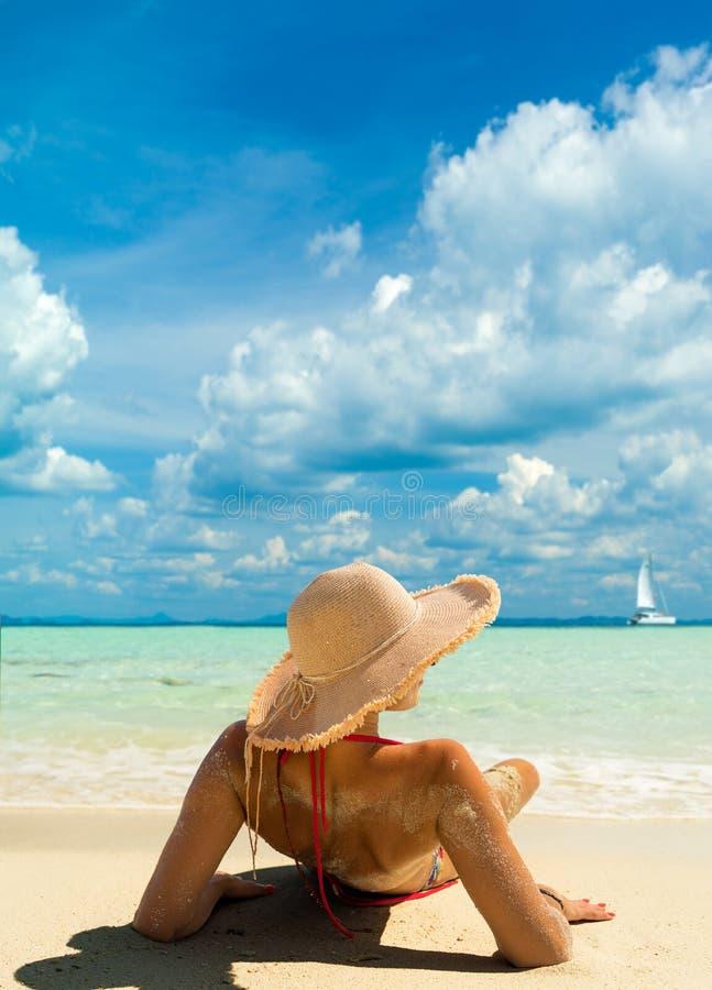 De vrouw van de de vakantiebikini van de strandbruine kleur het liggen het looien onder trop royalty-vrije stock foto