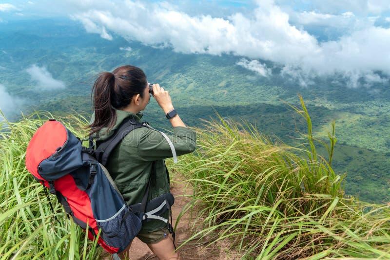 De vrouw van wandelaarazi? kijkt verrekijkers en status op berg Vrouwelijke avonturenrugzak en het kamperen op stijging in openlu stock afbeeldingen
