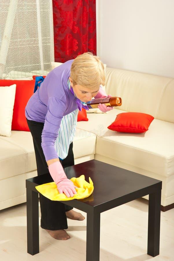 De vrouw veegt stof op de lijst af stock afbeelding