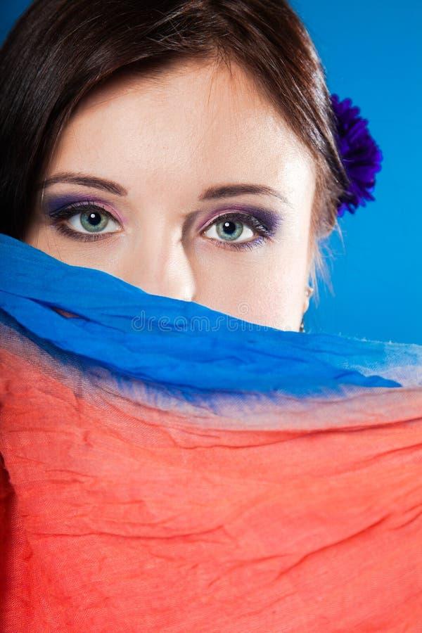De vrouw verbergt haar gezicht met sjaal op blauw stock fotografie