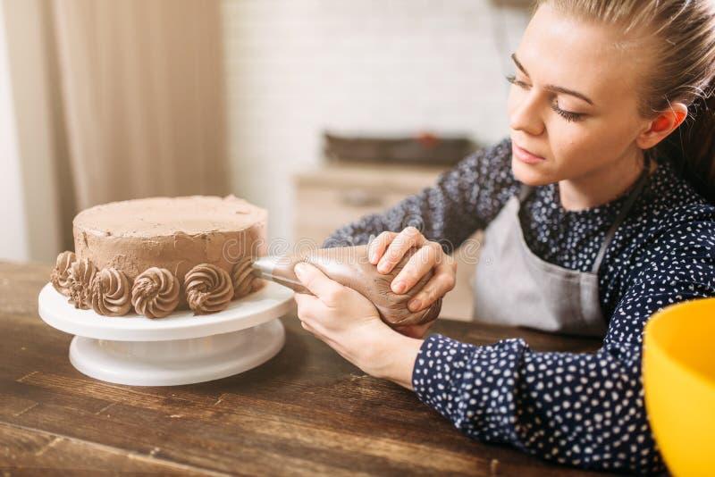 De vrouw verfraait cake met culinaire spuit royalty-vrije stock foto