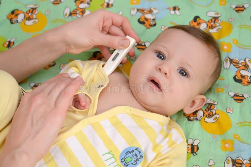 De vrouw vergt temperatuur aan de zieke baby elektronische ther royalty-vrije stock afbeelding