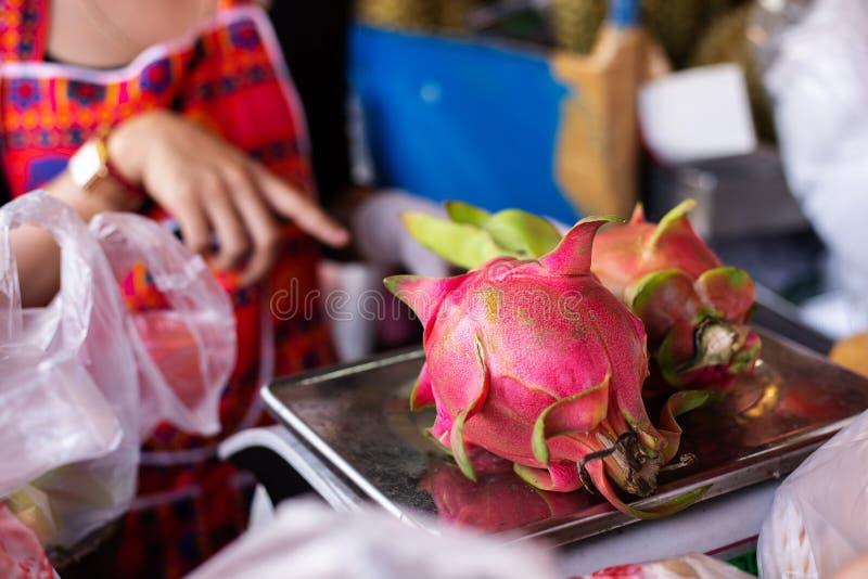 De vrouw verkoopt draakfruit op markt stock afbeeldingen