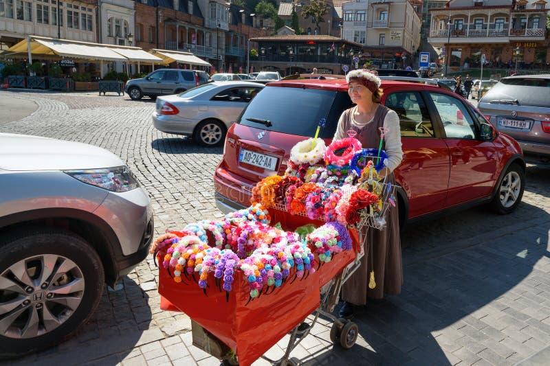 De vrouw verkoopt kronen van bloemen op hoofd Tbilisi georgië royalty-vrije stock fotografie