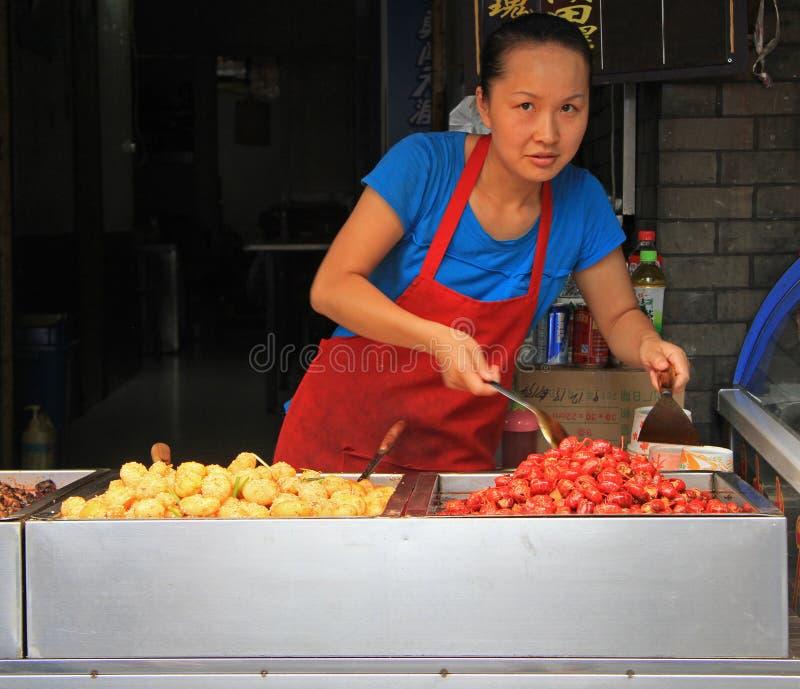 De vrouw verkoopt snacks openlucht in Wuhan, China stock foto