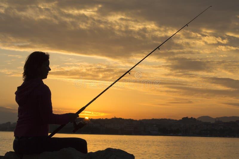 De vrouw vist op zee zonsondergang stock foto's