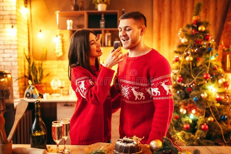 De vrouw voedt haar echtgenoot een Kerstmiscake stock afbeeldingen