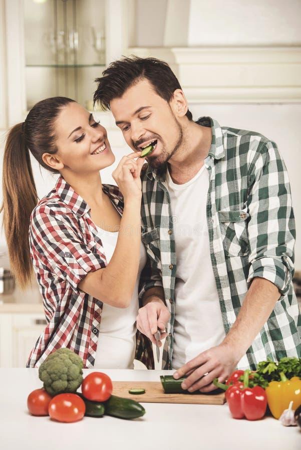 De vrouw voedt haar echtgenoot met komkommer in comfortabele keuken stock afbeeldingen